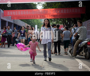 A mixed-race toddler runs ahead of her Chinese mother at a trade fair in a city in China. - Stockfoto