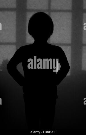Sweden, Silhouette of boy in dark room - Stock Photo