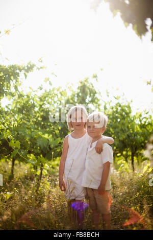 Italy, Tuscany, Portrait of sister (6-7) embracing younger brother (4-5) in orchard - Stockfoto