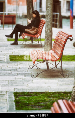 A young female adult reads a book on a red painted bench in the Dorsoduro district of Venice. - Stockfoto
