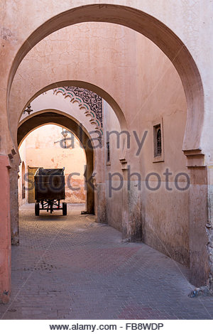 Mule and cart driving through pink plastered archways outside the former school, Medersa Ben Youssef in the Medina - Stock Photo