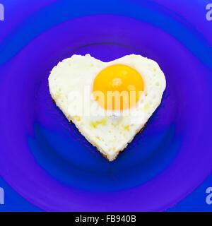 Heart shaped egg on blue dish - Stockfoto
