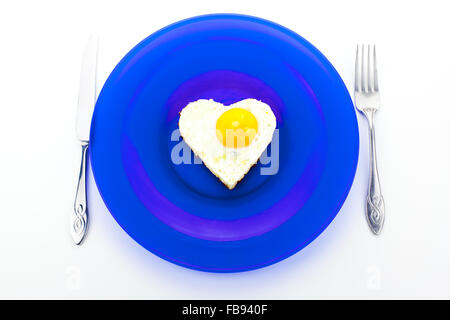 Valentine breakfast with heart shaped egg on a blue dish - Stock Photo