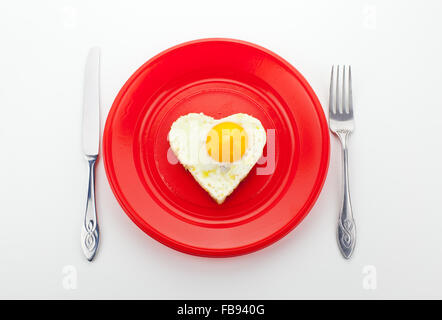 Valentine breakfast with heart shaped egg on a red dish - Stock Photo