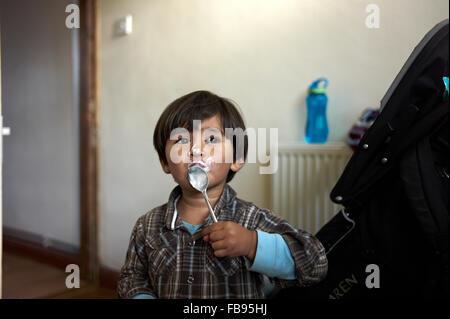 young mixed race boy eats yogurts - Stock Photo