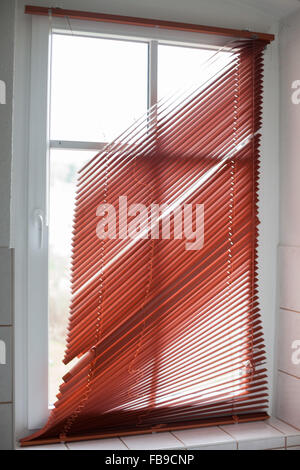 Broken red window blinds in a bathroom - Stock Photo