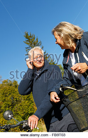 Sweden, Sodermanland, Man using mobile phone with woman - Stock Photo