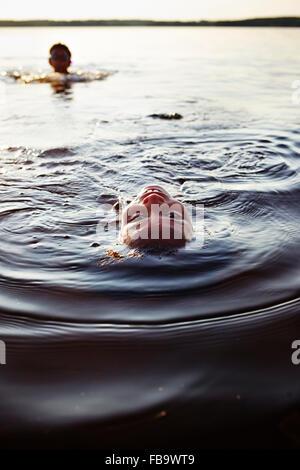 Sweden, Vastra Gotaland, Skagern, Children (6-7, 10-11) swimming in lake - Stockfoto
