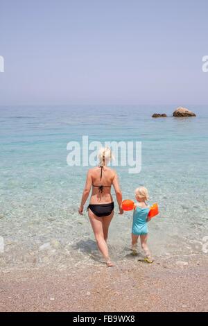 Greece, Karpathos, Amopi, Woman and girl (6-7) walking in sea - Stock Photo