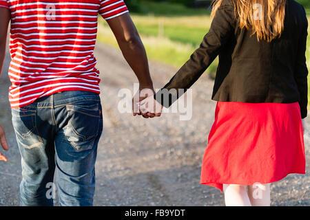 Sweden, Vastmanland, Bergslagen, Hallefors, Rear view of mid adult couple holding hands - Stock Photo