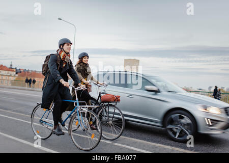 Sweden, Uppland, Stockholm, Vasatan, Sankt Eriksgatan, Man and woman cycling on city street - Stock Photo