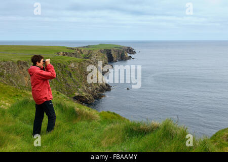 United Kingdom, Scotland, Shetland Islands, Unst, Senior woman standing at grassy cliff looking through binoculars - Stock Photo
