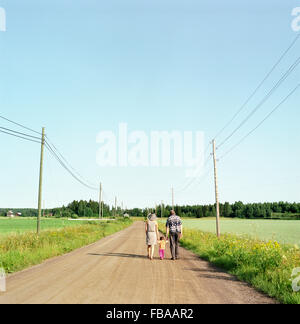 Finland, Uusimaa, Lapinjarvi, Rear view of people with child (2-3) walking along dirt road - Stock Photo