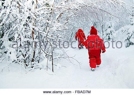 Finland, Keski-Suomi, Jyvaskyla, Girls (2-3, 6-7) walking on footpath in winter forest, rear view - Stockfoto