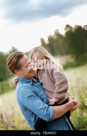 Finland, Uusimaa, Raasepori, Karjaa, Father holding in arms his daughter (6-7) - Stock Photo