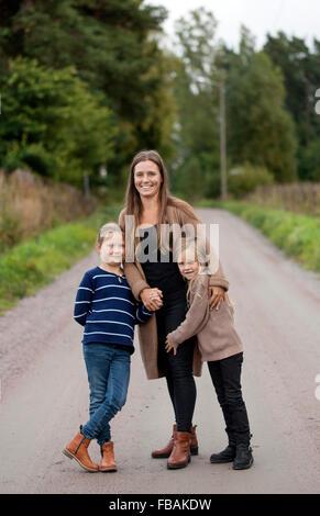 Finland, Uusimaa, Raasepori, Karjaa, Outdoor portrait of mother with two daughters (6-7) - Stock Photo