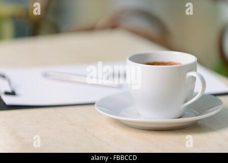 Cup of coffee standing on the table - Stock Photo