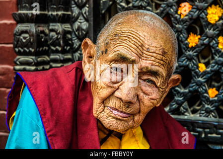Very old tibetan buddhist nun sitting outside a shrine in Kathmandu - Stock Photo