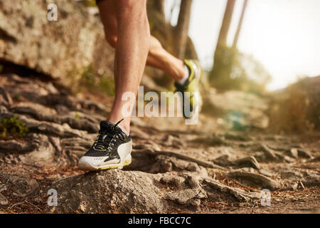 Close-up of trail running shoe on challenging rocky terrain. Male runner's legs working out on extreme terrain outdoors. - Stock Photo