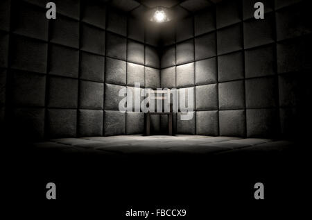 A dark dirty white padded cell in a mental hospital with an empty chair in the corner lit by a single spotlight - Stock Photo