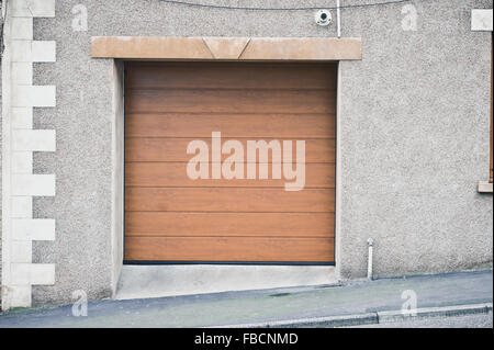 A closed wooden garage door in a stone wall of a house - Stock Photo