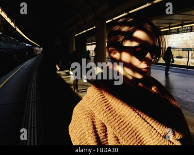 Close-Up Of Woman In Sunglasses Standing On Railroad Station Platform - Stock Photo