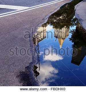 Reflection Of Building In Puddle - Stock Photo