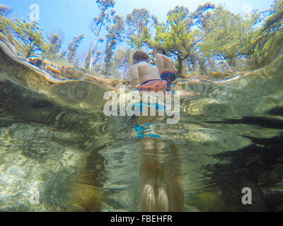 Low Angle View Of Shirtless Boy Standing In River - Stock Photo