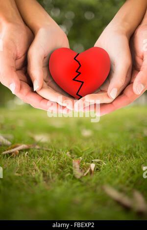 Zusammengesetztes Bild des Paares gebrochenes Herz in den Händen halten - Stockfoto