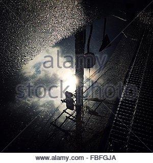 Reflection Of Telephone Pole In Puddle On Street During Rainy Season - Stock Photo