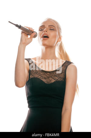 young pretty blond woman singing in microphone isolated close up black dress, karaoke girl - Stock Photo