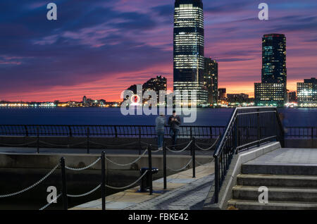 Long exposure view of the sunset with World Financial Plaza and two men standing, and Jersey City towers in the - Stock Photo