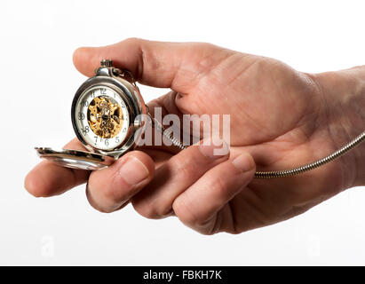 Man holding a vintage silver full hunter pocket watch in his hand opened to display the bronze mechanism through - Stock Photo