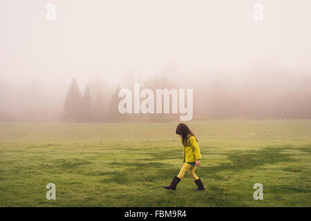 Side view of a Girl walking in park on a foggy day - Stock Photo