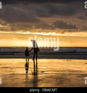 Mother and daughter holding hands at the beach - Stock Photo