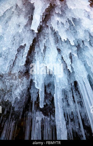 Icicles background on the ice wall on Baikal lake at winter - Stock Photo