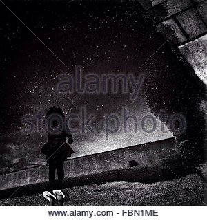 Reflection Of Girl On Puddle At Night - Stock Photo