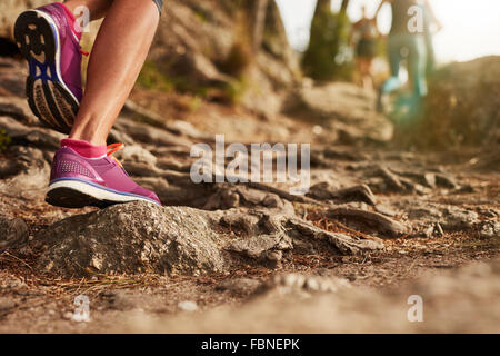 Close up of an athlete's feet wearing sports shoes on a challenging dirt track. Trail running workout on rocky terrain - Stock Photo