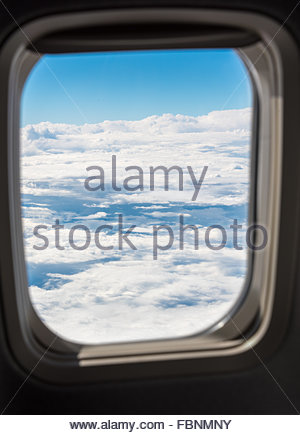Cloudscape from plane: Beautiful clouds and blue sky seen from airplane window over the United States in Summer - Stock Photo