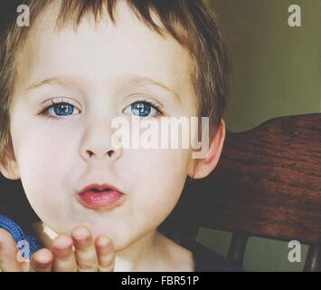 Portrait Of Cute Blue Eyed Boy Blowing A Kiss - Stock Photo