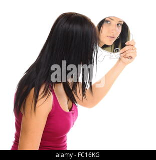 young woman looking at her face in mirror - Stock Photo