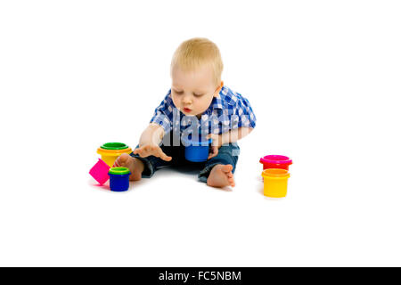baby boy on a white floor with toys - Stock Photo