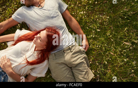 Young woman lying on the lawn with her boyfriend. Overhead view of young couple relaxing on the grass, with copy - Stock Photo
