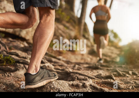 Closeup of male feet run through rocky terrain. Cross country running with focus on runner's legs. - Stock Photo