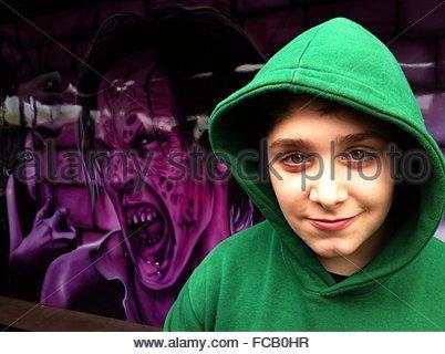 Portrait Of Teenage Boy Against Graffiti On Wall - Stock Photo