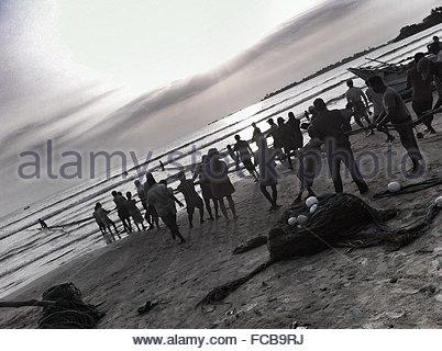 Tilt Image Of Fishermen Pulling Fishing Net On Beach Against Sky - Stockfoto