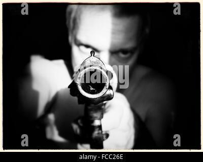 Man Aiming Gun At Camera - Stock Photo