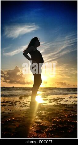 Full Length Of Pregnant Woman Standing On Beach Against Sky During Sunset - Stockfoto