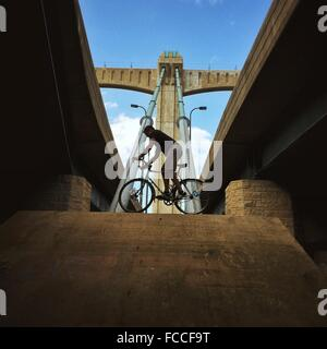 Low Angle View Of Man Balancing On Bicycle Along Bridge - Stock Photo