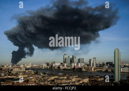 Black smoke cloud seen over Canary Wharf from a warehouse fire in east London, UK. - Stock Photo